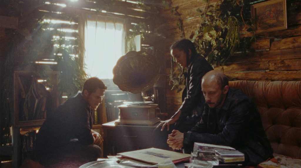 The three characters are in a decrepit room of a cabin, overgrown with vegetation that has crept indoors. Light is filtering through the spaces in between the wood and through the window offering a very misty quality to the photo. A youngish man with short hair is seating on the left of a vintage phonograph, a woman is standing up beside it with her hands on the desk where it is placed, and another man is seated beside her and looking at an album cover which is stacked on other album covers on a messy desk. They appear to be listening.